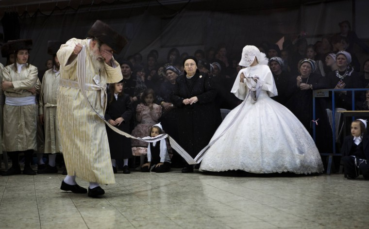 A Jewish bride dances with her grandfather, the Rabbi of the ultra-Orthodox Jewish group, Tholdot Avraham Yizhak Hasidic, during her wedding in Mea Shearim, an ultra-orthodox neighborhood of Jerusalem. During the Mitzva Tanz dance ritual members of the community and family dance in front of the bride at the end of the wedding ceremony. (Menahem Kahana/GettyImages)