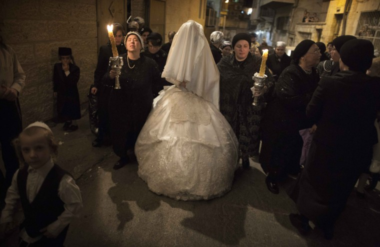 A Jewish bride (C) from the Ultra-Orthodox Tholdot Avraham Yizhak Hasidic group, is escorted by her family members to her wedding ceremony in the Ultra Orthodox neighborhood of Mea Shearim, in Jerusalem. (Menahem Kahana/GettyImages)