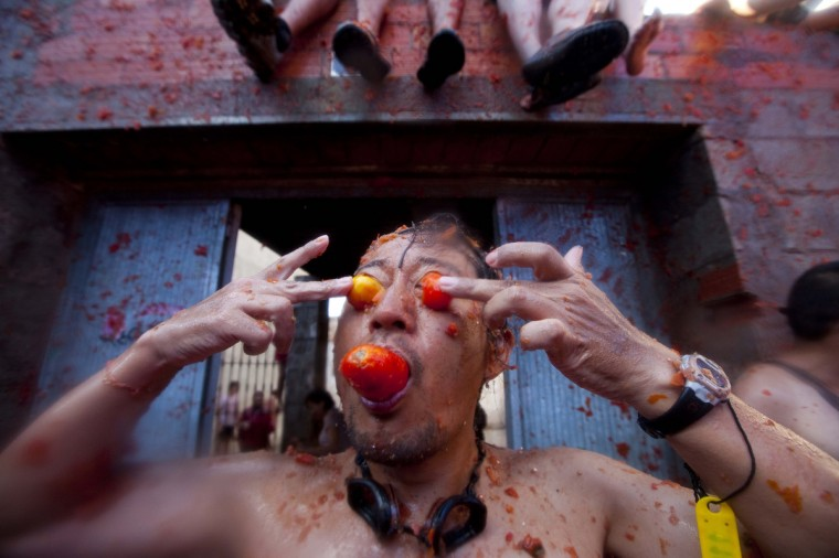 """Revelers take part in the annual """"tomatina"""" tomato fight fiesta in the village of Bunol, near Valencia. Tens of thousands of revelers hurled 120 tons of squashed tomatoes at each other, drenching the streets in red in a gigantic Spanish food fight known as the Tomatina. (Biel Alino/GettyImages)"""