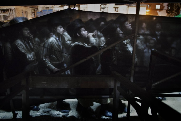 A group of Ultra-Orthodox Hasidic Jews are seen behind a curtain during the wedding ceremony of the granddaughter of the Rabbi of the Tholdot Avraham Yizhak Hasidic group, in the Ultra-Orthodox neighborhood of Mea Shearim, in Jerusalem. (Menahem Kahana/GettyImages)