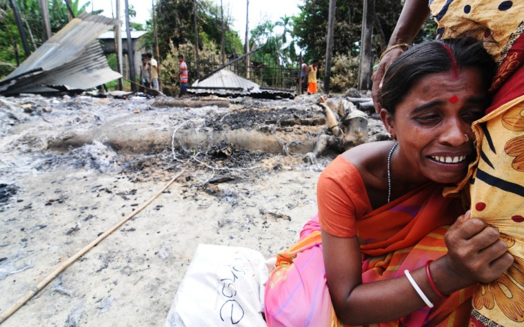 An Indian resident cries near the remains of her house burnt by rioters in Kharabari Charak Math village at Barpeta district, some 170km from Guwahati. Violence in Assam has spilled over to the neighboring Barpeta district as a rally by members of the All Assam Minority Students Union (AAMSU) turned violent killing one person and burning down five houses. (Biju Boro/GettyImages)