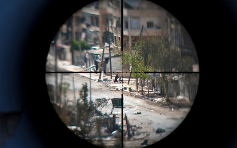 A woman and her baby are seen through the scope of an opposition fighter sniper gun, as she flees the Saif al-Dawla neighborhood of the Syrian northern city of Aleppo, amid heavy street fighting. The battle for Aleppo, Syria's second largest city, has lasted for over a month, with the army unable to dislodge the rebels. (Zac Baillie/GettyImages)