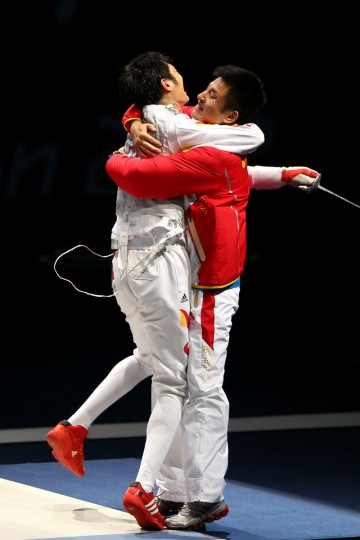 Sheng Lei of China celebrates with his coach after winning the Men's Foil Individual Gold Medal Bout against Alaaeldin Abouelkassem of Egypt on Day 4 of the London 2012 Olympic Games at ExCeL on July 31, 2012 in London, England. (Hannah Johnston/Getty Images)