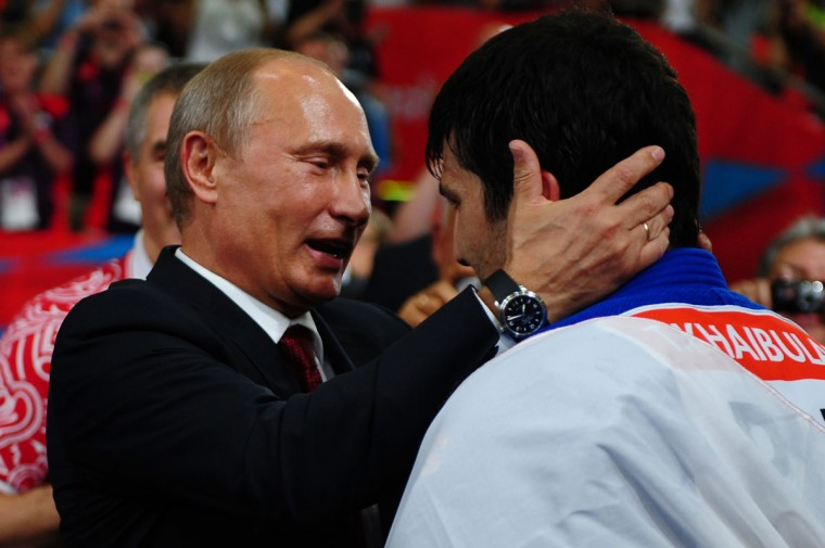 Russian President Vladimir Putin (C) celebrates Tagir Khaibulaev of Russia's gold medal in the Men's -100 kg Judo on Day 6 of the London 2012 Olympic Games at ExCeL on August 2, 2012 in London, England. (Laurence Griffiths/Getty Images)