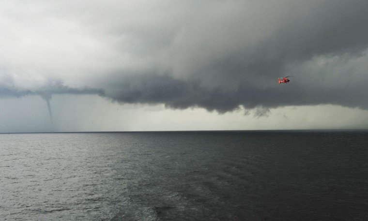 A Coast Guard Air Station Atlantic City MH-65 Dolphin helicopter takes part in deck landing qualifications with the Coast Guard Cutter Diligence as a water spout forms behind of August 1, 2012 off the coast of Atlantic City, New Jersey. (Nick Ameen/U.S. Coast Guard/Getty Images)
