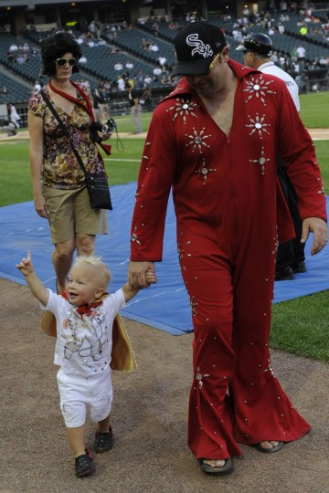 August 3, 2012: A man and child dressed like Elvis walk on the field during a parade of Elvis' on Elvis Night before the game between the Chicago White Sox and the Los Angeles Angels of Anaheim at U.S. Cellular Field in Chicago, Illinois. (David Banks/Getty Images)