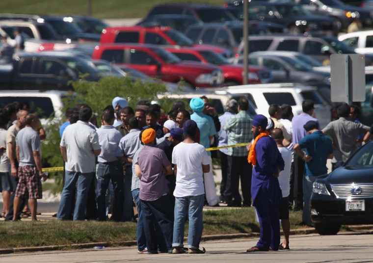 OAK CREEK, WI - AUGUST 05: People wait for word on family and friends in front of the Sikh Temple of Wisconsin where at least one gunman fired upon people at a service August, 5, 2012 Oak Creek, Wisconsin. At least six people were killed when a shooter, who was later shot dead by a police officer, opened fire on congregants in the Milwaukee suburb. (Scott Olson/Getty Images)