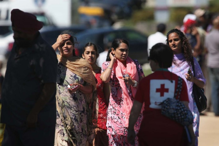 OAK CREEK, WI - AUGUST 5: People look on in front of the Sikh Temple of Wisconsin where at least one gunman fired upon people at a service August, 5, 2012 Oak Creek, Wisconsin. At least six people were killed when a shooter, who was later shot dead by a police officer, opened fire on congregants in the Milwaukee suburb. (Scott Olson/Getty Images)