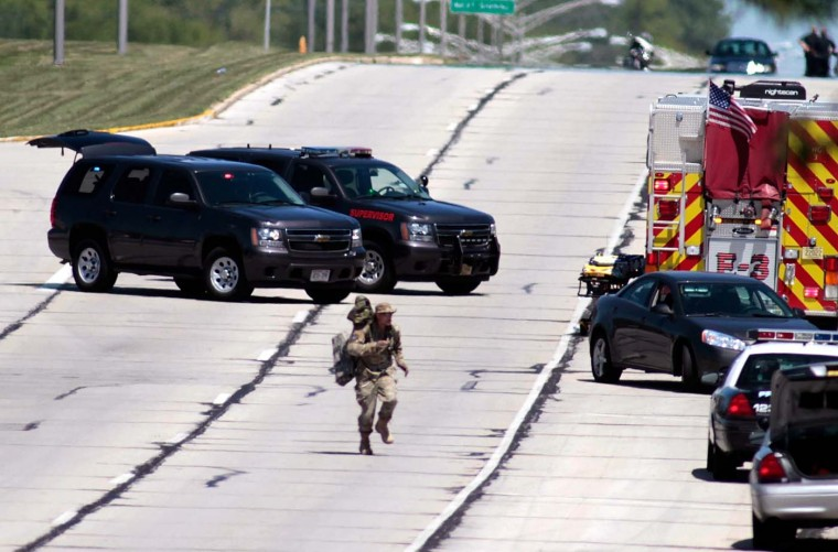 OAK CREEK, WI - AUGUST 5: A tactical officer runs to position as SWAT officers surround the Sikh Temple of Wisconsin where at least one gunman fired upon people at a service August, 5, 2012 Oak Creek, Wisconsin. At least six people were killed when a shooter, who was later shot dead by a police officer, opened fire on congregants in the Milwaukee suburb. (Darren Hauck/Getty Images)