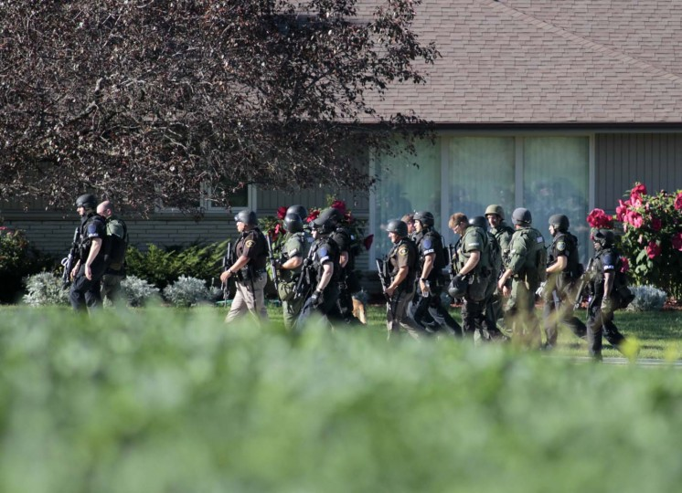 OAK CREEK - AUGUST 5: Various police personnel walk away from the site just outside of where swat teams had surrounded the Sikh Temple of Wisconsin where a gunman stormed the mass and opened fire August, 5, 2012 Oak Creek, Wisconsin. At least six people were killed when a shooter opened fire on congregants in the Milwaukee suburb. The shooter who was later shot dead by a police officer. (Darren Hauck/Getty Images)