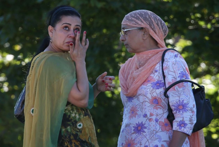 OAK CREEK, WI - AUGUST 05: A woman wipes away a tear in front of the Sikh Temple of Wisconsin where at least one gunman stormed the mass and opened fire August, 5, 2012 Oak Creek, Wisconsin. (Scott Olson/Getty Images)
