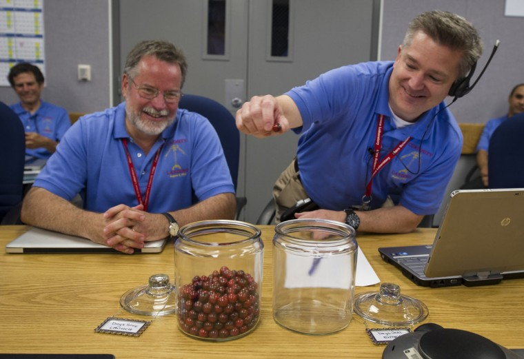 "August 5, 2012: Mars Science Laboratory (MSL) Flight Systems Chief Engineer Rob Manning (L) smiles as he watches MSL Flight Director Keith Comeaux move the final marble from a jar marked ""Days Until Entry"" to the jar marked ""Days Since Launch"" at the Jet Propulsion Laboratory in Pasadena, California. (Bill Ingalls/NASA via Getty Images)"