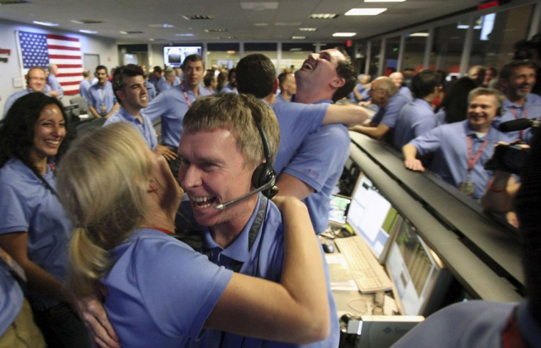 August 5, 2012: Telecom engineer Peter Ilott hugs a colleague, celebrating a successful landing inside the Spaceflight Operations Facility for NASA's Mars Science Laboratory Curiosity rover at Jet Propulsion Laboratory in Pasadena, California. (Brian van der Brug-Pool/Getty Images)