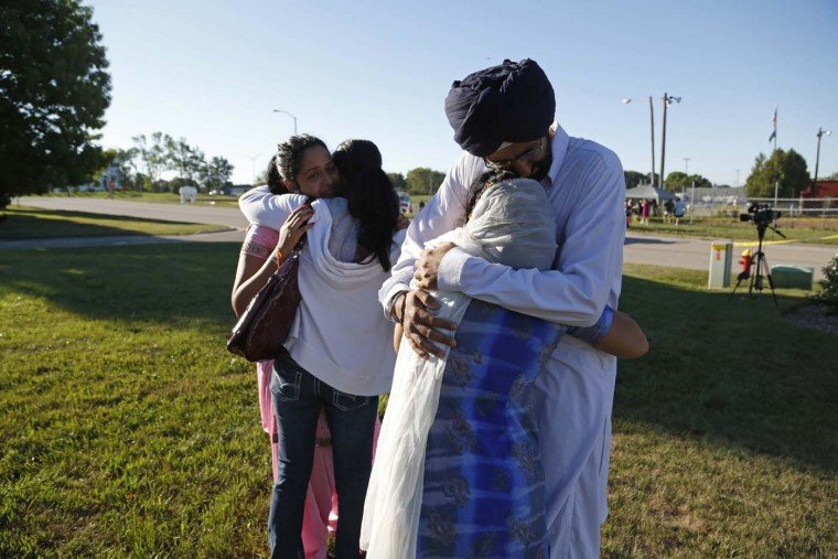 OAK CREEK - AUGUST 6: People console each other at the command center near the Sikh Temple of Wisconsin where yesterday a gunman fired upon people at service August, 6, 2012 Oak Creek, Wisconsin. (Darren Hauck/Getty Images) 149967350