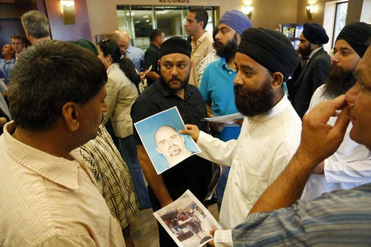 OAK CREEK - AUGUST 6: Members of the community hold up the mug shot handed out by the FBI of the suspected shooter Wade Michael Page after a press conference on the shooting at the Sikh Temple of Wisconsin where yesterday a gunman fired upon people at service August, 6, 2012 in Oak Creek, Wisconsin. (Darren Hauck/Getty Images)