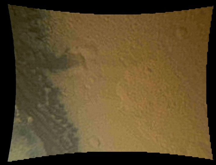 August 6, 2012: This color thumbnail image was obtained by NASA's Curiosity rover during its descent to the surface of Mars and transmitted to Spaceflight Operations Facility for NASA's Mars Science Laboratory Curiosity rover at Jet Propulsion Laboratory (JPL) in Pasadena, California. This image from Curiosity's Mars Descent Imager reveals surface features including relatively dark dunes, degraded impact craters and other geologic features including small escarpments that range in size from a few feet (meters) to many tens of feet (meters) in height. The image was obtained one minute 16 seconds before touchdown. (NASA/JPL-Caltech/MSSS/Getty Images)