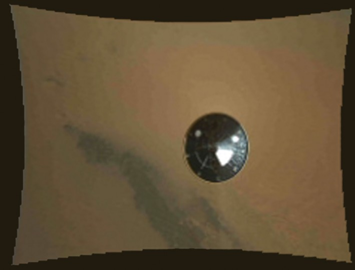 August 6, 2012: This color thumbnail image was obtained by NASA's Curiosity rover during its descent to the surface of Mars and transmitted to Spaceflight Operations Facility for NASA's Mars Science Laboratory Curiosity rover at Jet Propulsion Laboratory (JPL) in Pasadena, California. The image was obtained by the Mars Descent Imager instrument known as MARDI and shows the 15-foot (4.5-meter) diameter heat shield when it was about 50 feet (16 meters) from the spacecraft. It was obtained two and one-half minutes before touching down on the surface of Mars and about three seconds after heat shield separation. The resolution of all of the MARDI frames is reduced by a factor of eight in order for them to be promptly received on Earth during this early phase of the mission. Full resolution (1,600 by 1,200 pixel) images will be returned to Earth over the next several months as Curiosity begins its scientific exploration of Mars. (NASA/JPL-Caltech/MSSS/Getty Images)