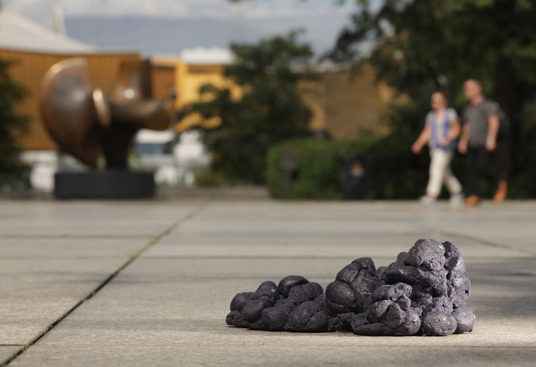 "Visitors walk past one of four piles of fake blue horse manure outside the Neue Nationalgalerie art museum in Berlin, Germany. The four piles are an art installation by artist Martin Gostner titled ""The Oriel of the Blue Horses"" that refers to the Expressionist painting ""The Tower of the Blue Horses,"" which has been missing since it was confiscated by the Nazis in 1937. (Sean Gallup/Getty Images)"