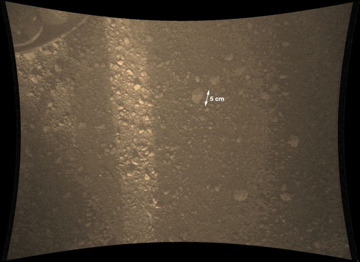 August 8, 2012: A new full-resolution color image from NASA's Curiosity Rover shows the pebble-covered surface of Mars. It was taken by the Mars Descent Imager (MARDI) several minutes after Curiosity touched down. The camera is about 30 inches (70 centimeters) from the surface as the rover sits on the ground. A sliver of sunlight passing through the structure of the rover illuminates the surface. The largest rock fragment in the image is about 2 inches (5 centimeters) long. Most are much smaller. A rover wheel is visible at the top left. (NASA/JPL-Caltech/MSSS/Getty Images)