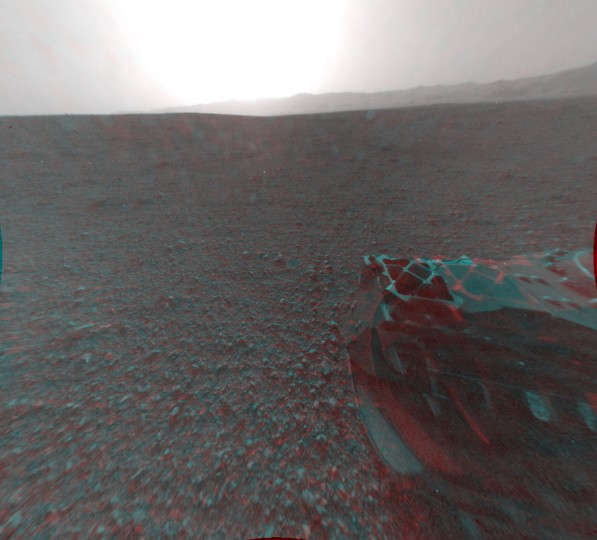 August 8, 2012: A new 3-D image shows the view behind NASA's Curiosity rover, which landed on Mars on August 5. The anaglyph was made from a stereo pair of Hazard-Avoidance Cameras on the rear of the rover. Part of the rim of the Gale Crater, which is the size of Connecticut and Rhode Island combined, stretches from the top middle to the top right of the image. One of the rover's wheels can be seen at bottom right. The bright spot is saturation from the sun. (NASA/JPL-Caltech/Getty Images)