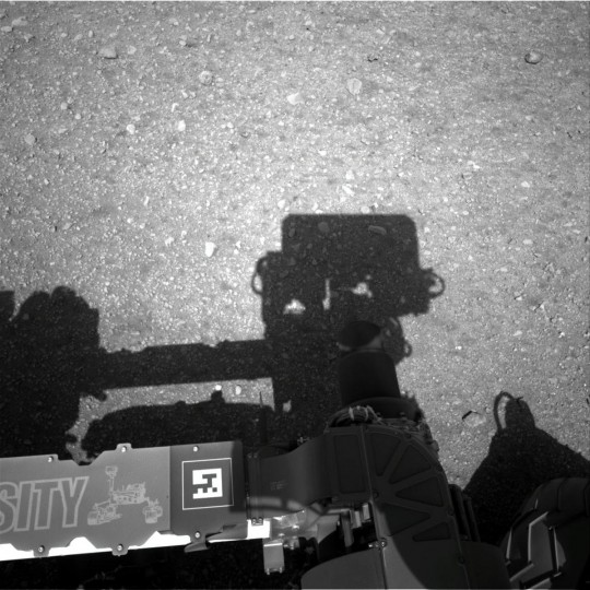August 8, 2012: This is the first image taken by the Navigation cameras on NASA's Curiosity rover. It shows the shadow of the rover's now-upright mast in the center, and the arm's shadow at left. The arm itself can be seen in the foreground. The navigation camera is used to help find the sun -- information that is needed for locating, and communicating, with Earth. After the camera pointed at the sun, it turned in the opposite direction and took this picture. The position of the shadow helps confirm the sun's location. (NASA/JPL-Caltech/Getty Images)