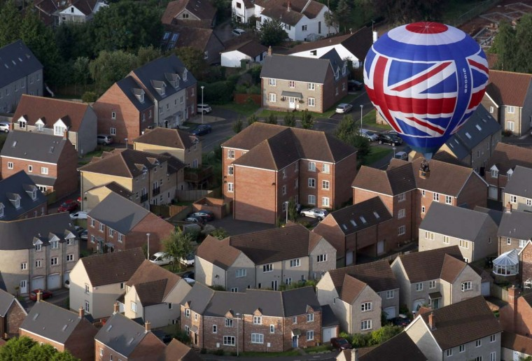 A hot air balloon flies from Ashton Court over houses at the Bristol International Balloon Fiesta in Bristol, England. The fiesta is Europe's largest annual hot air balloon event, in the city that is seen by many balloonists as the home of modern ballooning. (Matt Cardy/Getty Images)