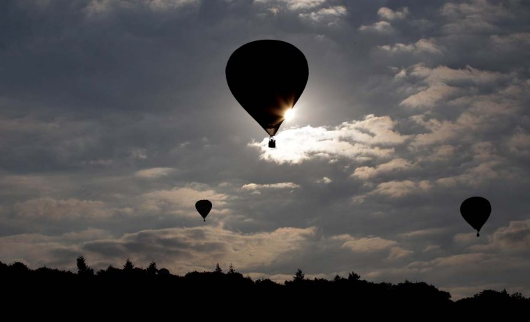 Balloons silhouetted in the morning light take to the skies from Ashton Court at the Bristol International Balloon Fiesta in Bristol, England. The early morning flight of nearly 100 balloons over the city was the first mass ascent of the four-day Bristol International Balloon Fiesta. (Matt Cardy/Getty Images)