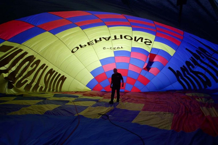 A balloonist prepares a hot air balloon as balloons take to the skies from Ashton Court at the Bristol International Balloon Fiesta in Bristol, England. (Matt Cardy/Getty Images)