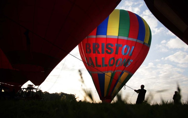 A silhouetted balloonist prepares a hot air balloon as balloons take to the skies from Ashton Court at the Bristol International Balloon Fiesta. The early morning flight of nearly 100 balloons over the city was the first mass ascent of the four-day Bristol International Balloon Fiesta. (Matt Cardy/Getty Images)