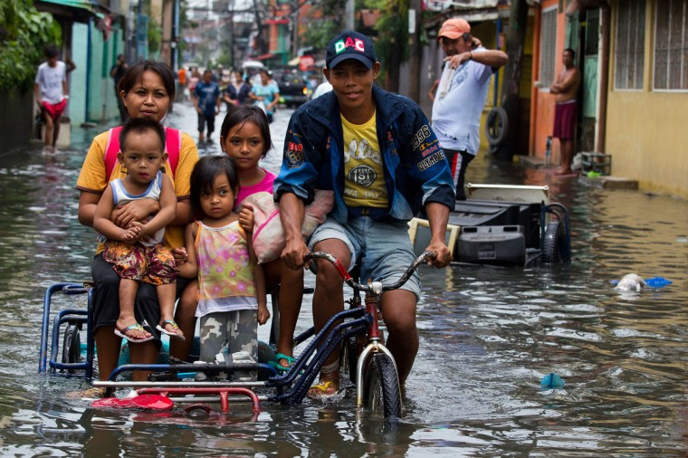 Flood victims stand get transported down a flooded city street in Manila, Philippines. The death toll has climbed to more than 100 people as metro Manila dealt with nearly 2 weeks of monsoon rains effecting more than 2 million people, the worst flooding in 3 years. Phillippine residents are starting to return to their homes and cleaning up the storm damage. (Paula Bronstein/Getty Images)