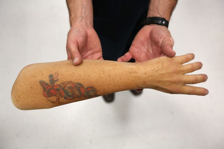 Certified prosthetist Robert Kuenzi holds a life-like sleeve for a prosthetic arm at the Center for the Intrepid (CFI), at Brooke Army Medical Center, on August 7, 2012 in San Antonio, Texas. Artists paint the rubber covers, complete with custom tatoos, which slide over prosthetic arms and legs made at the center for military amputees. The CFI is the largest rehabilitation center for wounded military service members suffering from amputations, burns and functional limb loss in the United States. Thousands of war wounded, most injured in Afghanistan and previously in Iraq, spend months, if not years, in outpatient care at the CFI. (John Moore/Getty Images)