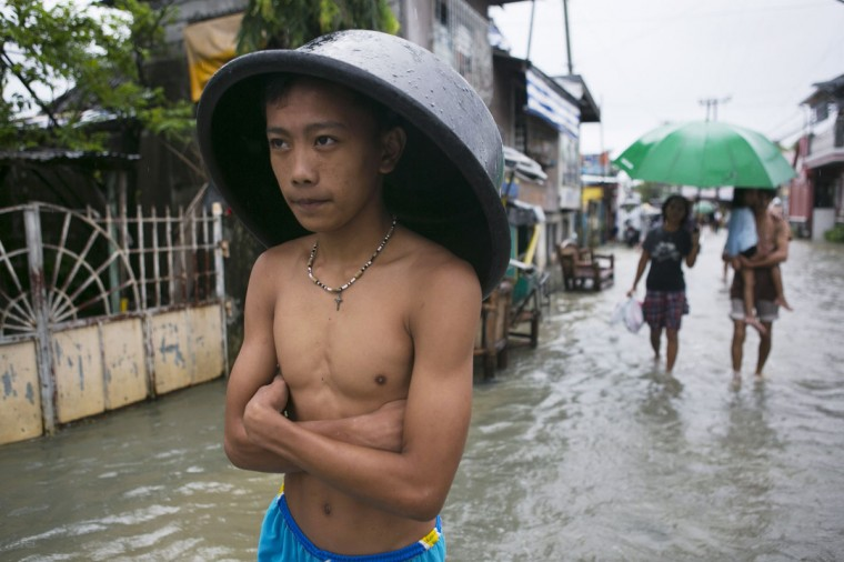 A man covers his head with a bucket as more rain falls in the flooded coastal region in Bulacan, Philippines. According to the Office of Civil Defense, the floods have left at least 96 people dead with the flooding effecting up to 2.68 million people, including more than 440,000 fleeing to evacuation centers, in Manila and surrounding provinces. (Paula Bronstein/Getty Images)