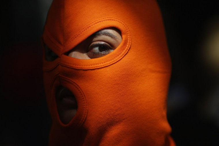 LONDON, ENGLAND - AUGUST 17: A person wears an orange mask as a demonstration by supporters of the jailed feminist punk band 'Pussy Riot' takes place outside the Russian Embassy on August 17, 2012 in London, England. The three women who staged an anti-Kremlin protest in a church in February, were found guilty today of hooliganism motivated by religious hatred, and could face a three-year jail sentence. Supporters are gathering in several cities around the world today as a mark of solidarity. (Dan Kitwood/Getty Images)