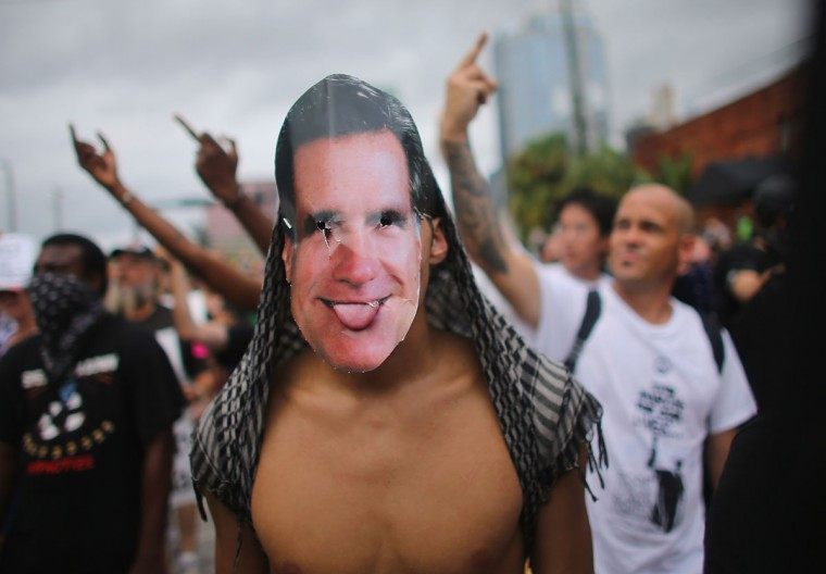 A protester wears a Mitt Romney mask as he and other protesters walk through the streets before the start of the Republican National Convention being held at the Tampa Bay Times Forum on August 27, 2012 in Tampa, Florida. (Joe Raedle/Getty Images)