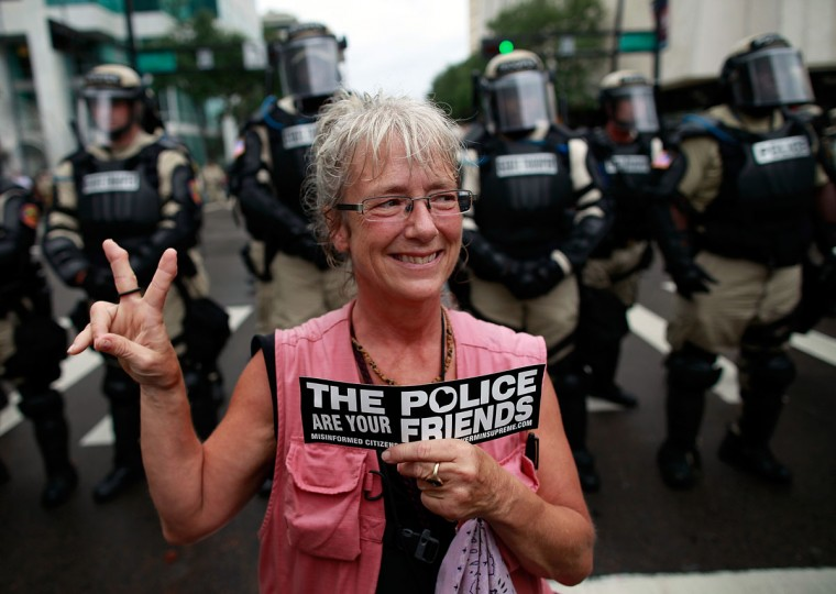 An activist makes a peace sign in front of law enforcement officers while demonstrating on August 27, 2012 in Tampa, Florida. (Tom Pennington/Getty Images)