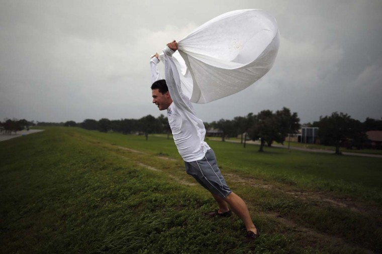 Matthew Pettus holds a sheet open in the wind on the levee near Lake Pontchatrain as Hurricane Isaac approaches. (Chris Graythen/Getty Images)