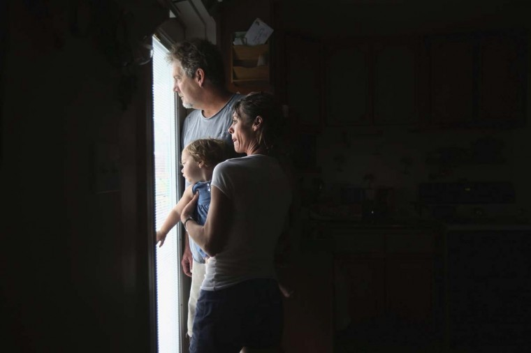 Bridgette Mooney, her daughter Skyler, 15 months, and husband Kevin watch from their home as Hurricane Isaac lashes their property with rain in Kiln, Mississippi. Many residents of the community, which suffered severe damage during Hurricane Katrina in 2005, decided to stay home and ride out the storm. (John Moore/Getty Images)