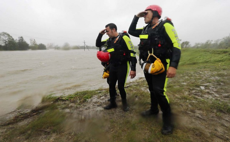 Rescue workers look out at floodwaters from a levee in Braithwaite, Louisiana. Dozens were reportedly rescued in the area in Plaquemines Parish after levees were overtopped by floodwaters from Hurricane Isaac. (Mario Tama/Getty Images)