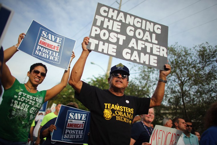 "Protesters walk together during a march that was put on by West Central Florida Federation of Labor to, in their words, ""demonstrate the reality of Mitt Romney's America"" as the Republican National Convention continues at the Tampa Bay Times Forum on August 29, 2012 in Tampa, Florida. (Joe Raedle/Getty Images)"