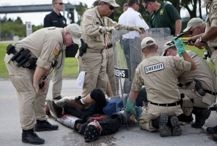 Law enforcement officials work to free protesters with Earth First who had connected themselves to each other in front of the Big Bend TECO Power Station in Apollo Beach, Florida. The protesters came from marching against the Republican National Convention in Tampa, Florida most of the week. (Photo by Edward Linsmier/Getty Images)