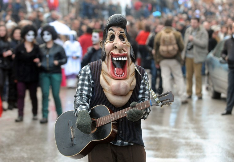 January 13, 2012: A reveller with an Elvis Presley mask takes part in a carnival parade through south-western Macedonian village of Vevchani. The Vevchani carnival is 1,400 years old and is held every year on the eve of the feast of Saint Basil (14th of January), which also marks the beginning of the New Year according to the Julian calendar. The masks are handmade and they usually present pagan rituals, bible issues and political satire of actual events. (Robert Atanasovski/AFP/Getty Images)