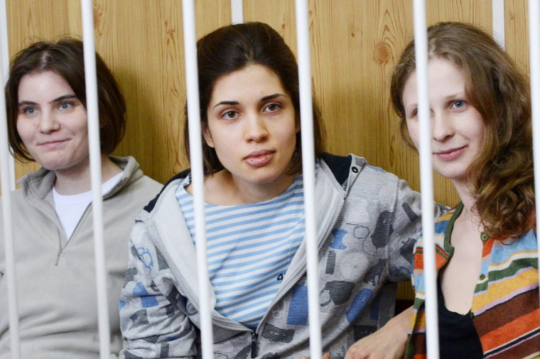 "MOSCOW, RUSSIA - JULY 20: Members of the all-girl punk band ""Pussy Riot"" Nadezhda Tolokonnikova (C), Maria Alyokhina (R) and Yekaterina Samutsevich (L), sit behind bars during a court hearing in Moscow on July 20, 2012. (Natalia Kolesnikova/AFP/Getty Images)"