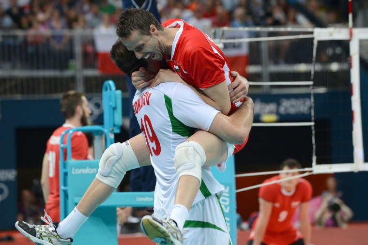 Bulgaria's Teodor Salparov celebrates victory with an unidentified player in the Men's Preliminary Pool A volleyball match between Poland and Bulgaria in the 2012 London Olympic Games in London on July 31, 2012. (Kirill Kudryavtsev/AFP/Getty Images)
