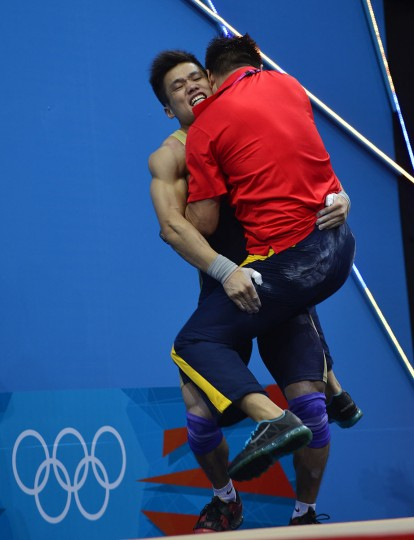 China's Lu Xiaojun (L) celebrates with his coach during the men's 77kg group A weightlifting event during the London 2012 Olympic Games at The Excel Centre in London on August 1, 2012. (Yuri Cortez/AFP/Getty Images)