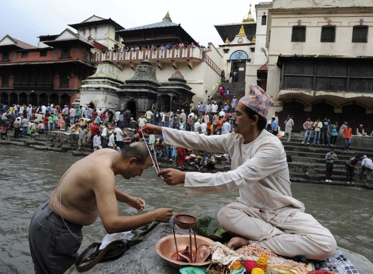 A Nepalese Hindu devotee ( L) receives a Janai (sacred thread) from a Hindu Brahmin on the occasion of the Janai Purnima Festival, also known as Rakshya Bandhan, at the Pashupatinath temple in Kathmandu on August 2, 2012. (Prakash Mathema/AFP/Getty Images)