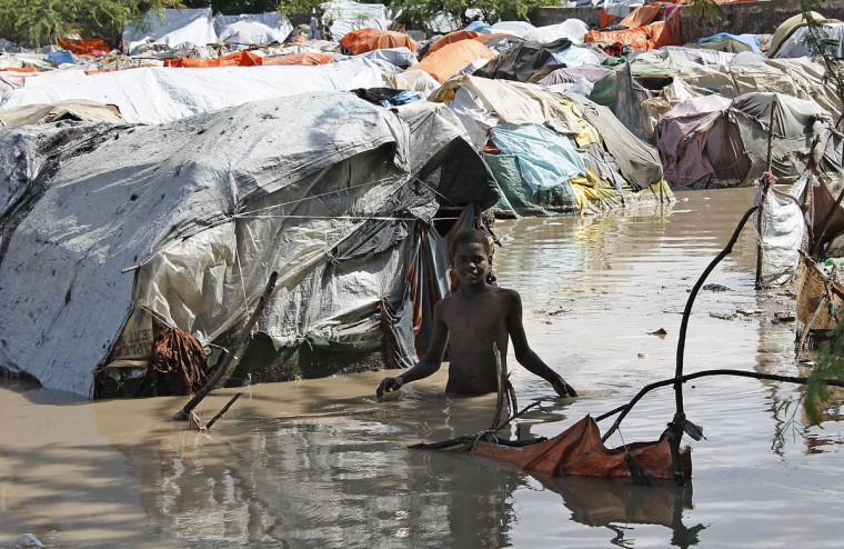 A Somali internally displace person, wades through water at an IDP camp among the cloth and twig shelters, following heavy rain and flash floods in the Somali capital, Mogadishu. (Mohamed Abdiwahab/AFP/Getty Images)