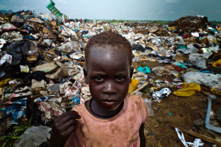 A picture taken on August 1, 2012 shows a young Sudanese posing at a rubbish dump in the South Sudanese capital, Juba. The increase of prices in South Sudan makes life very difficult for South Sudanese people, some of them have no other choice but to pick up food or find and sell iron from rubbish dump areas. (Camille Lepage/AFP/Getty Images)