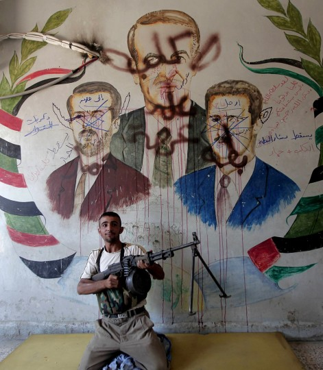 A Syrian rebel poses in front of a vandalized mural depicting Syrian President Bashar al-Assad (R), his late father and predecessor Hafez al-Assad (C) and his late brother Bassel al-Assad in the northern city of Aleppo on. Shells rained down on rebel positions in Aleppo ahead of a UN vote to deplore both the Syrian regime's use of heavy arms and world powers for failing to agree on steps to end the conflict. (Ahmad Gharabli/AFP/Getty Images)
