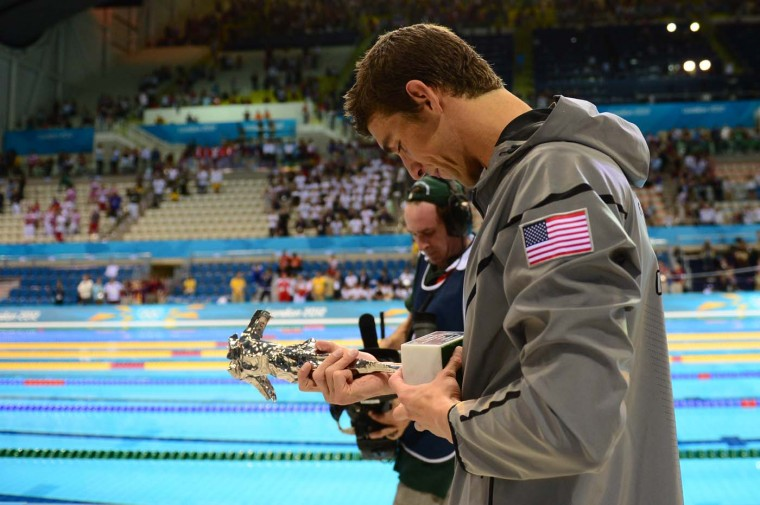 U.S. swimmer Michael Phelps looks at his trophy of the greatest olympic athlete of all time after he won gold in the men's 4x100m medley relay final during the swimming event at the London 2012 Olympic Games on August 4, 2012 in London. (Martin Bureau/AFP/Getty Images)
