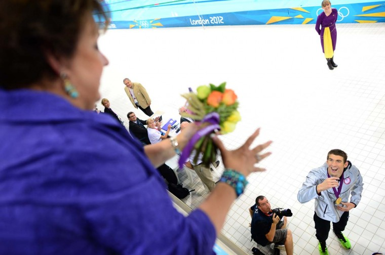 U.S. swimmer Michael Phelps throws flowers to his mother Debbie after he won gold in the men's 4x100m medley relay final during the swimming event at the London 2012 Olympic Games on August 4, 2012 in London. (Christophe Simon/AFP/Getty Images)